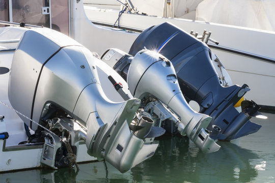 A row of three outboard engines in rest at port