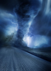 Powerful Tornado with debris on a road. Lightning illuminates the tornado.