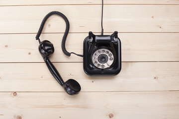 Old retro black phone on wooden board, top view, DOF, focus on phone