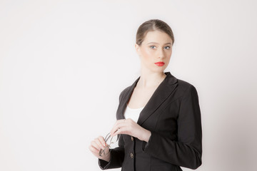 Portrait of business woman with glasses on a white background. Business girl in suit on the background wall.