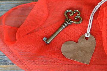 Brown suede heart and old key on red fabric background