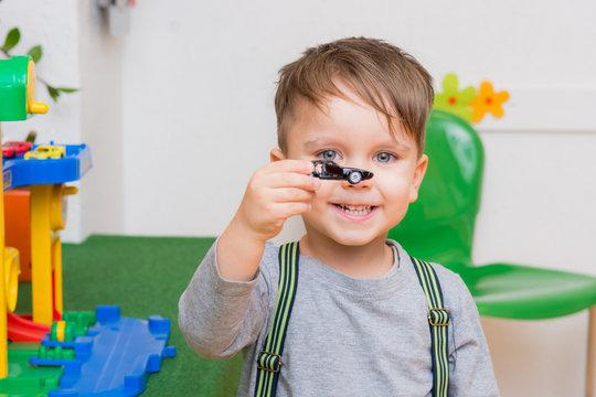 kleiner junge spielt mit autos im kindergarten