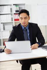 geschäftsmann am arbeitsplatz schaut auf seinen laptop