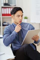 junger geschäftsmann liest konzentriert am tablet