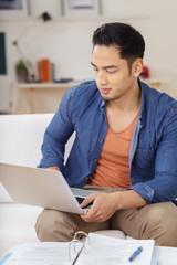student arbeitet mit laptop und unterlagen zu hause