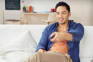lächelnder mann mit fernbedienung auf dem sofa