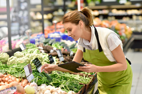 Supermarket employee putting vegetables in shelves