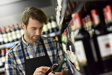 Wine specialist putting bottle up in winery section of supermarket