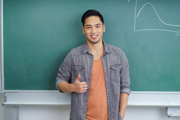 student vor der tafel zeigt daumen hoch