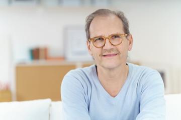 lächelnder älterer mann mit brille in seiner wohnung