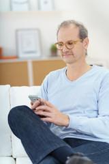 älterer mann sitzt auf dem sofa und liest eine nachricht auf seinem smartphone
