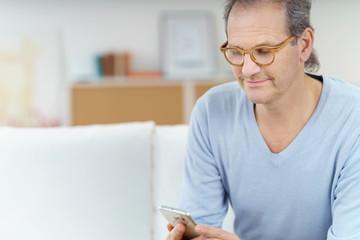 älterer mann liest eine nachricht auf seinem handy