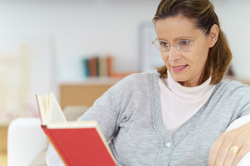 ältere frau liest ein buch in ihrer wohnung