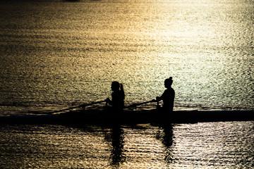 Weibliche Ruderer auf See im Sonnenuntergang