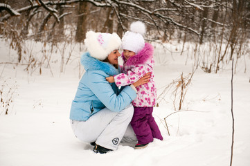 Mother and her little daughter enjoying beautiful winter day out