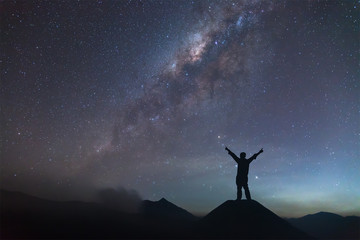 Man is spreading hand on hill and seeing the Milky Way.