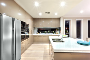A modern kitchen with refrigerator and fixed to the wall with ca