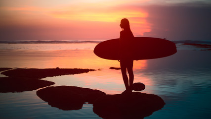 Silhouette surfer woman in bikini on tropical beach holding surfboard at sunset