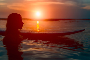 Silhouette surfer woman with surfboard at sunset