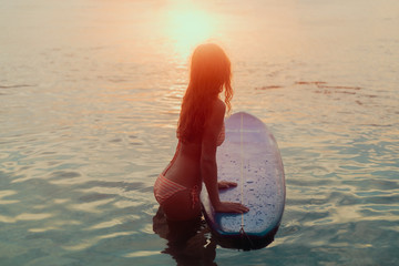 Rear view of beautiful sexy young woman surfer girl in bikini with blue surfboard on a beach at sunset or sunrise