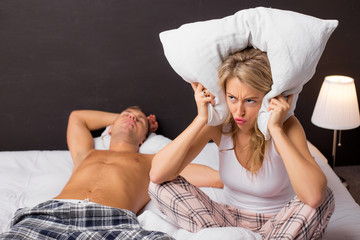 Woman covering her ears with pillow because her boyfriend is snoring