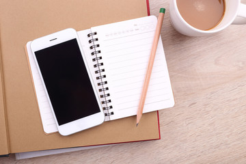 Blank screen smartphone with pencil and note book on wooden back