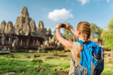 Wall Mural - Female tourist taking picture of Bayon temple in Angkor Thom