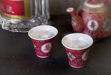 Sake wine cups, bottle on the background