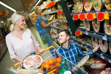 Spouses choosing pizza in store.