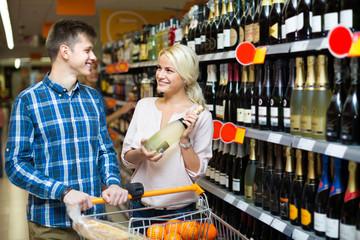 Family choosing wine at food shop