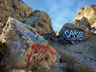 Rocky boulders with graffiti and blue sky - landscape photo