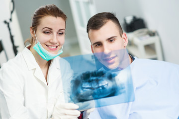 Doctor and patient looking at roentgen of human jaw, focus is on roentgen. Dentist office.