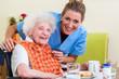 Pflegerin mit Seniorin beim Essen im Seniorenheim