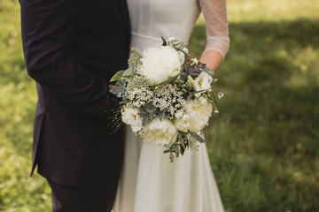 bride and groom holding a bouquet for a walk