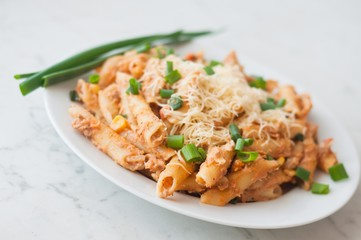 Penne pasta with healthy tuna fish, cheese and chopped scallion or spring onion leaves. Served on a white oval plate