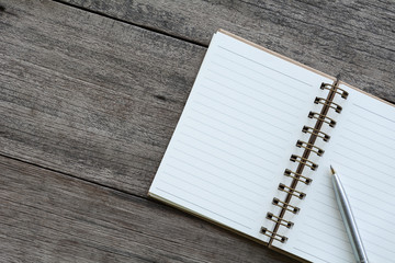 Notebook and pen on the wooden floor.