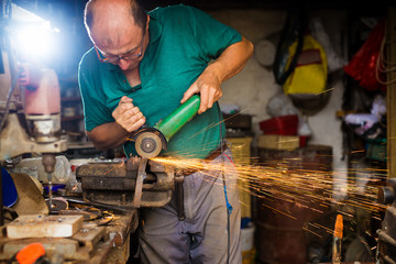 Craftsman sawing metal with disk grinder in workshop. Shallow depth of field.