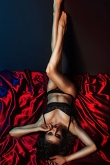 Sexy and hot brunette woman lying on red silk in seductive lace