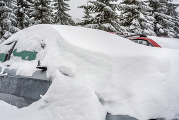 Car covered with snow in the winter
