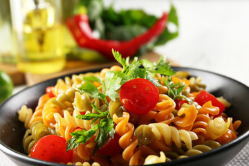 Delicious macaroni dish in black bowl on served grey wooden table