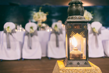 Vintage lantern lighting in front of party background.