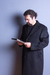 Man Wearing Trench Coat Reading from Tablet