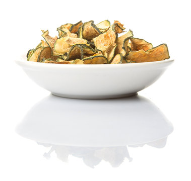 Dried zucchini or courgette in white bowl over white background
