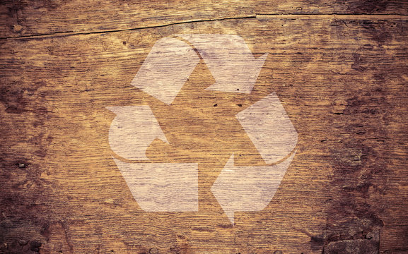 Recycling symbol on  rough wooden background