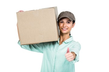 Cheerful delivery woman holding pack showing thumb up