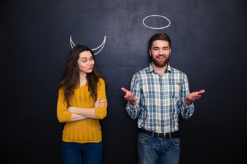 Happy couple playing devil and angel over blackboard background