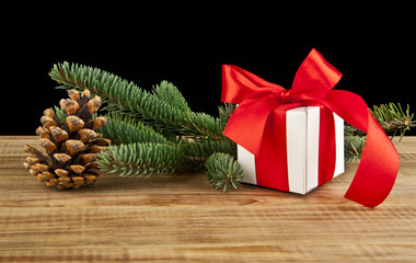 Christmas gift box and fir tree branch on wooden table