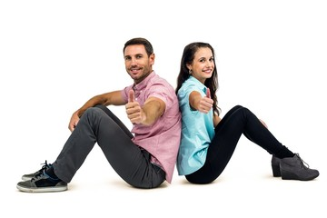 Smiling couple sitting showing thumbs up