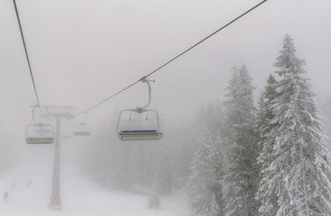 Chairs of a ski lift heading into the fog