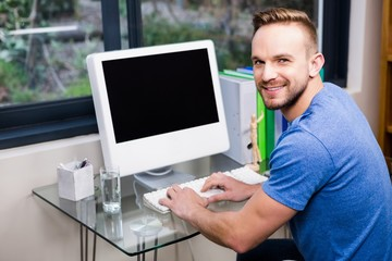 Smiling handsome man using computer